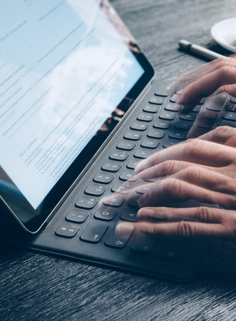 Closeup view of male hands fast typing on electronic tablet keyboard-dock station. text information on device screen. Man working at office.Vertical.