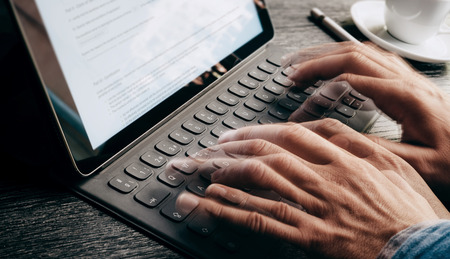Closeup view of male hands quickly typing on electronic tablet keyboard-dock station. text information on device screen. Man working at office.Horizontal,cropped. Stock Photo