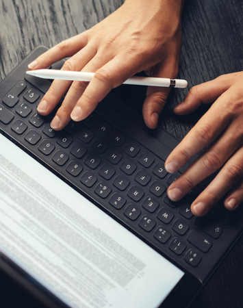 Closeup view of two male hands typing on electronic tablet keyboard-dock station. Man working at office and using electronic pen.Vertical.Cropped. 版權商用圖片
