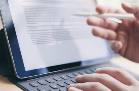 Blogger working mobile touchpad for work.Closeup view of male hands typing electronic tablet keyboard-dock station and using stylus pen.Horizontal.Blurred background. Stock Photo