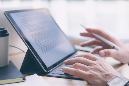 Blogger working at studio.Closeup view of male hands typing on electronic tablet keyboard-dock station.Business text information on device screen. Horizontal.Blurred background.