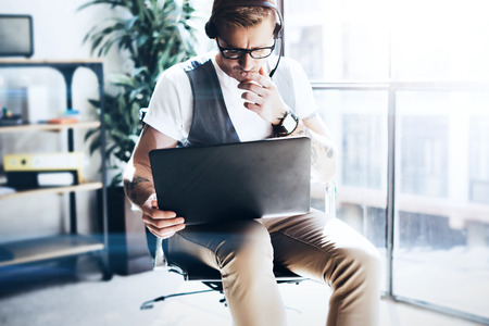 Businessman working on his digital tablet holding in hands. Elegant man wearing audio headset and making video conversation via digital tablet.Blurred background. Stock Photo