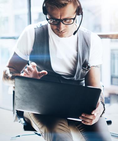 Businessman working on his digital tablet holding in hands. Elegant man wearing audio headset and making video conversation via digital tablet.Blurred background.Vertical.