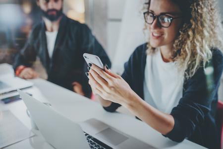 Mitarbeiter, die Prozessfoto bearbeiten Junges Mädchen in den Brillen, die zusammen mit bärtigem Kollegen am modernen Bürodach der Nacht arbeiten Teamwork-Konzept Unscharfer Hintergrund Horizontale Nahaufnahme.