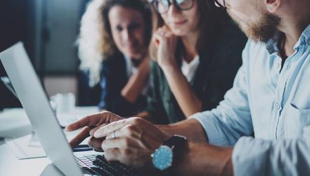 オフィスでチームワーク プロセスの概念。夜の近代的なオフィスのロフトで一緒に若いチーム作業。背景をぼかし。Horizontal.Cropped。