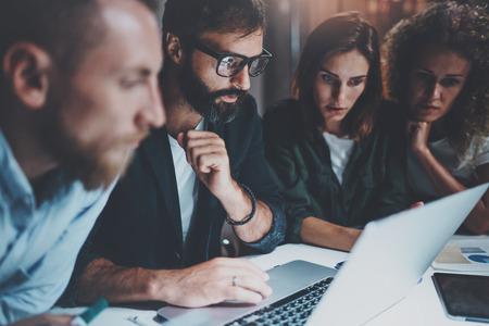 Arbeitsprozess im Büro Junge Leute, die Gespräch mit Partnern im Nachtbüro machen horizontal Unscharfer Hintergrund geerntet Standard-Bild