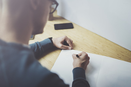 Skilled designer caucasian man drawing abstract sketch with pen.Art work process.Creative hobby.Noting ideas in copy book on workspace desk with papers in modern studio with panoramic windows.Closeup