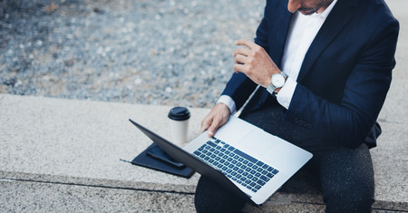 Attractive elegant businessman using contemporary notebook and smartphone sitting outside.Blurred background. Horizontal.Cropped Banque d'images