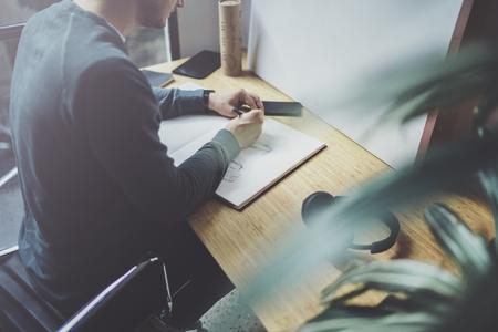 Bekwame ontwerper Kaukasische mens die abstracte schets met pen trekken Het werkproces van de kunst Creatieve hobby. Het opmerken van ideeën in exemplaarboek op werkruimtebureau met documenten in moderne studio met panoramische vensters.