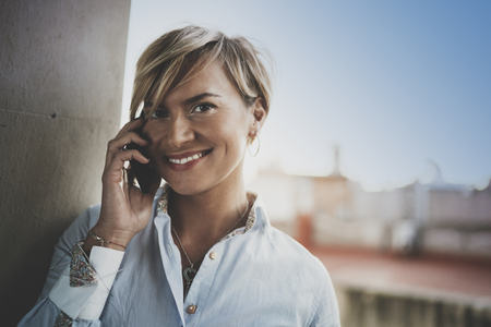 Portrait of smiling businesswoman talking with partner on smartphone device while working remotely in business travel.Attractive woman owner communicating on cellular while looking at camera.Blurred.