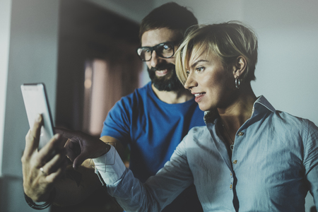 Happy family couple using smartphone in livingroom at home.Bearded man in eye glasses making selfie with young blonde woman at home. Blurred background.
