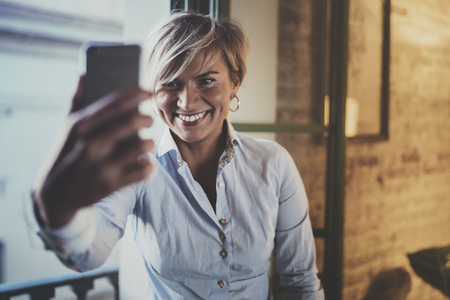 Smiling young girl making selfie on smartphone device while spending time in living room.Attractive woman owner communicating on cellular phone.Blurred background.