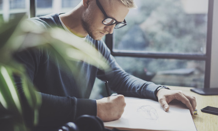 Skilled designer caucasian man drawing abstract sketch with pen.Art work process.Creative hobby.Noting ideas in copy book on workspace desk with papers in modern studio with panoramic windows.Blurred.