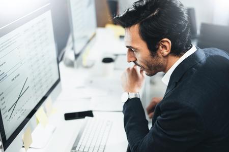 Biznesmen pracuje w biurze słoneczny na komputerze stacjonarnym siedząc przy stole. Niewyraźne tło, poziome.