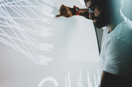 Concept of virtual panel display,diagram,digital graph interfaces.Young man touching virtual panel with graphs.Blurred background. Horizontal. Banco de Imagens