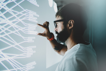 Concept of virtual panel display,diagram,digital graph interfaces.Attractive coworker touching virtual panel with graphs.Blurred background. Horizontal.
