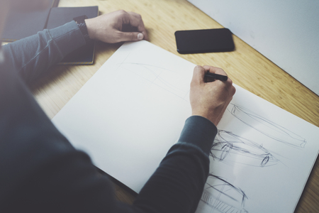 Skilled designer caucasian man drawing abstract sketch with pen.Art work process.Creative hobby.Noting ideas in copy book on workspace desk with papers in modern studio with panoramic windows.Closeup.