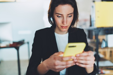 Closeup portrait of Businesswoman using smartphone while working at office.Blurred background.