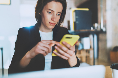 Closeup portrait of young Businesswoman using smartphone while working at office.Blurred background. Stock Photo