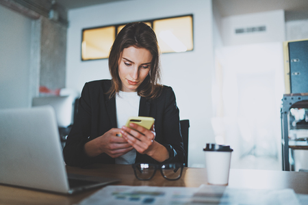 Smiling young businesswoman typing text message on smartphone while working at office.Blurred background.