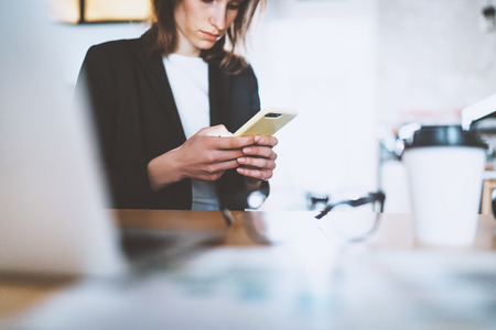Attractive young businesswoman typing text message on smartphone while working at office.Blurred background. Stock Photo