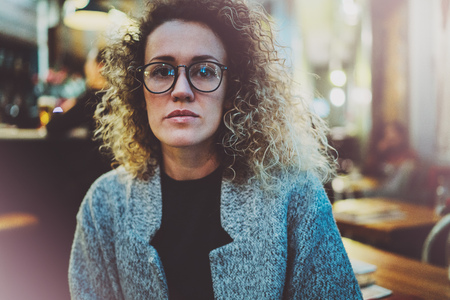 Pensive woman in stylish clothing wearing eye glasses outside in the european night city. Bokeh and flares effect on blurred background. 스톡 콘텐츠