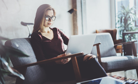 Attractive young businesswoman wearing casual clothes and working at coworking office.Female using contemporary mobile laptop while sitting in comfort armchair.