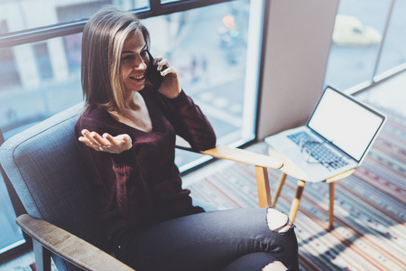 Attractive young businesswoman talking with partner via modern telephone while sitting in comfort armchair at modern meeting room.