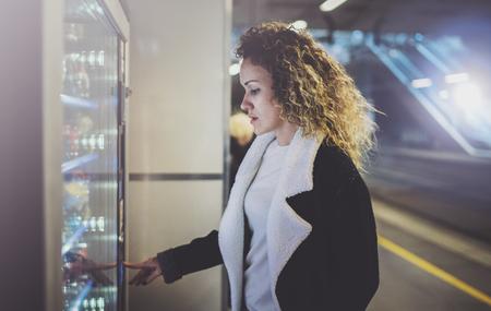 Mujer atractiva en la plataforma de tránsito utilizando una máquina expendedora de bebidas moderna. Su mano se coloca en el teclado de marcación y ella está mirando en la pequeña pantalla.