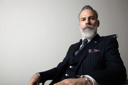Portrait of positive bearded gentleman wearing trendy suit over empty gray background. Copy Paste space. Studio shot