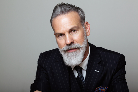 Portrait of attractive bearded gentleman wearing trendy suit over empty gray background. Studio shot, fashion concept.