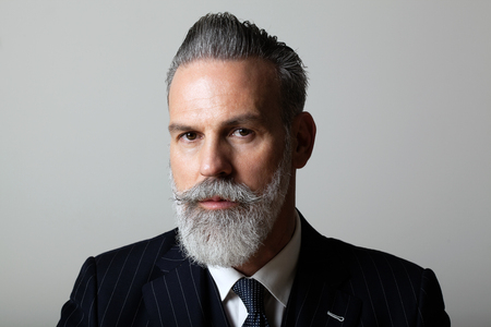 Portrait of elegant middle aged bearded gentleman wearing trendy suit over empty gray background. Studio shot, business fashion concept. Imagens