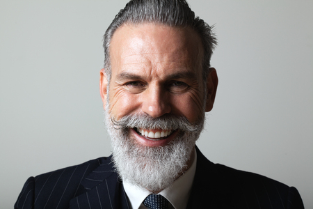 Portrait of happy middle aged bearded gentleman wearing trendy suit over empty gray background. Studio shot, business fashion concept. Imagens
