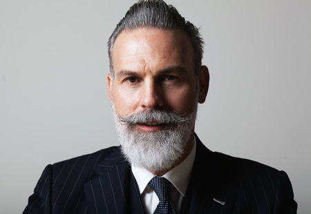 Portrait of handsome middle aged bearded gentleman wearing trendy suit over empty gray background. Studio shot, business fashion concept. Imagens - 103008762
