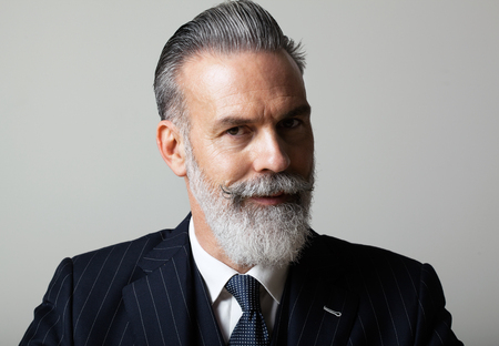 Portrait of pensive middle aged bearded gentleman wearing trendy suit over empty gray background. Studio shot, business fashion concept. Imagens - 102948205
