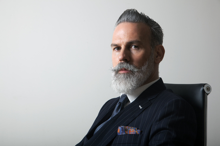 Portrait of confident bearded middle aged gentleman wearing trendy suit over empty gray background. Copy Paste space. Studio shot