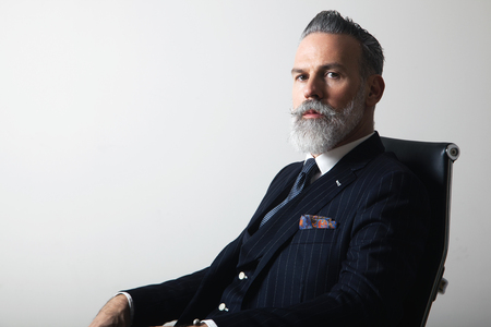 Portrait of positive bearded middle aged gentleman wearing trendy suit over empty gray background. Copy Paste space. Studio shot