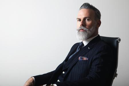 Ritratto di positivo barbuto gentiluomo di mezza età che indossa abito alla moda su sfondo grigio vuoto. Copia Incolla spazio. Studio girato Archivio Fotografico