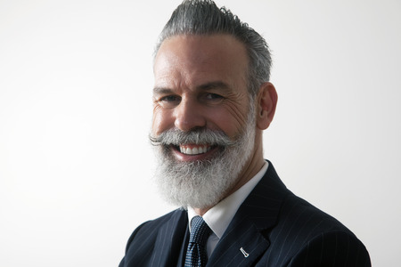 Closeup portrait of happy bearded middle aged gentleman wearing trendy suit over empty white background. Studio shot. Horizontal.
