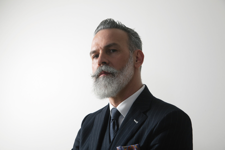 Portrait of confident bearded middle aged gentleman wearing trendy suit over empty white background. Studio shot. Horizontal. Imagens - 103474474