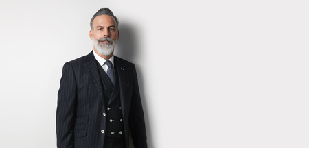 Portrait of bearded handsome businessman wearing trendy suit over empty white background. Copy Paste text space. Wide.