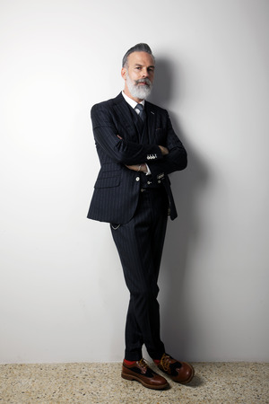 Portrait of confident bearded middle aged gentleman wearing trendy suit standing over empty white background. Studio shot. Vertical Imagens