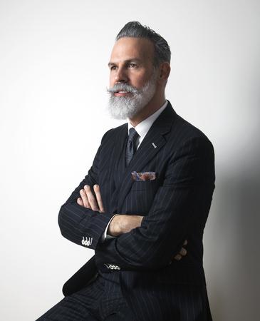 Portrait of attractive bearded middle aged gentleman wearing trendy suit over empty gray background. Studio shot. Vertical Imagens - 103474477