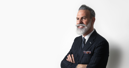 Portrait of bearded attractive gentleman wearing trendy suit over empty white background. Copy Paste text space. Wide.