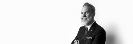 Portrait of bearded attractive gentleman wearing trendy suit over empty white background. Copy Paste text space. Wide. Black and White Imagens - 103474482