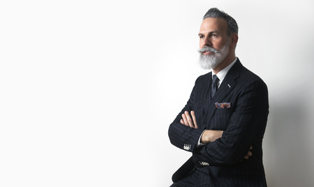 Portrait of bearded attractive gentleman wearing trendy suit over empty white background. Copy Paste text space.