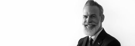 Portrait of bearded smiling gentleman wearing trendy suit over empty white background. Copy Paste text space. Wide. Black and White Imagens