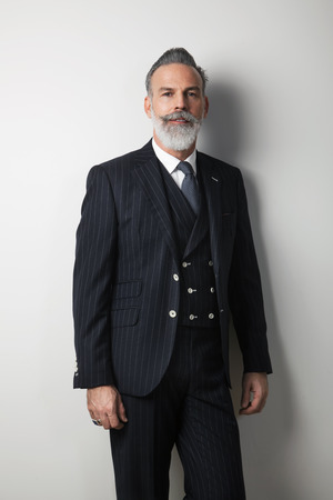 Portrait of confident bearded middle aged gentleman wearing trendy suit over empty white background. Studio shot. Vertical