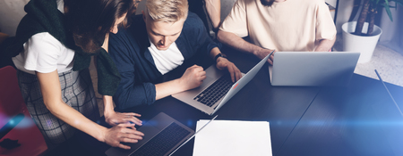 Coworkers team at work. Group of young business people in trendy casual wear working together in creative office.Wide.