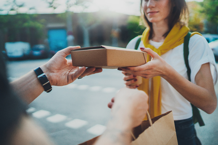 Mensajero masculino con bicicleta entregó la bolsa de compras sin nombre al cliente. Servicio de entrega de alimentos a domicilio.